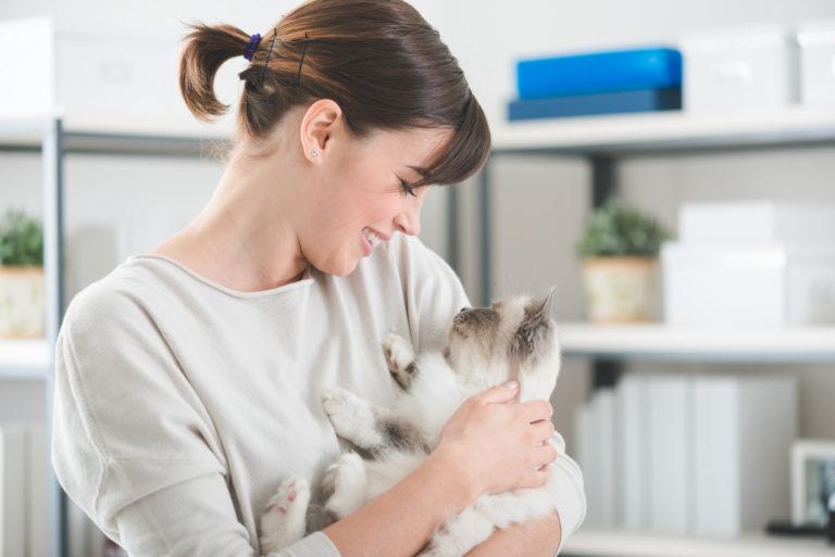 Jeune femme qui tient un chaton blanc et gris dans ses bras