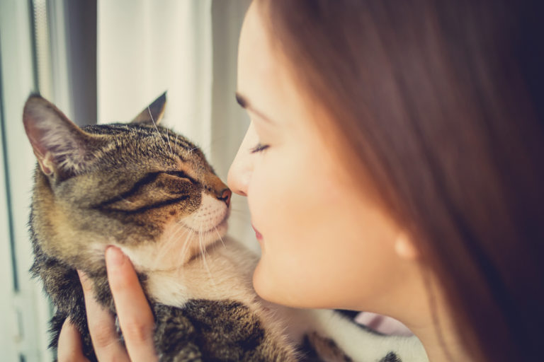 Jeune femme qui porte un chat et met son nez contre le museau du chat