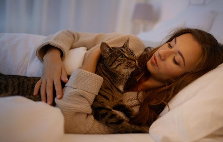 femme couchée dans son lit qui tient son chat dans ses bras