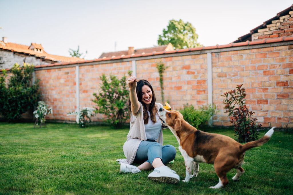 Une jeune femme joue avec son chien dans le jardin.